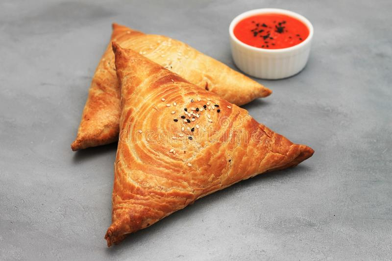 Delicious meat samosas and red sauce on gray background royalty free stock photography