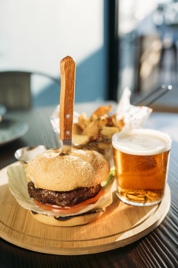 Delicious meet burger, fries and sauce served on wooden planks stock photo