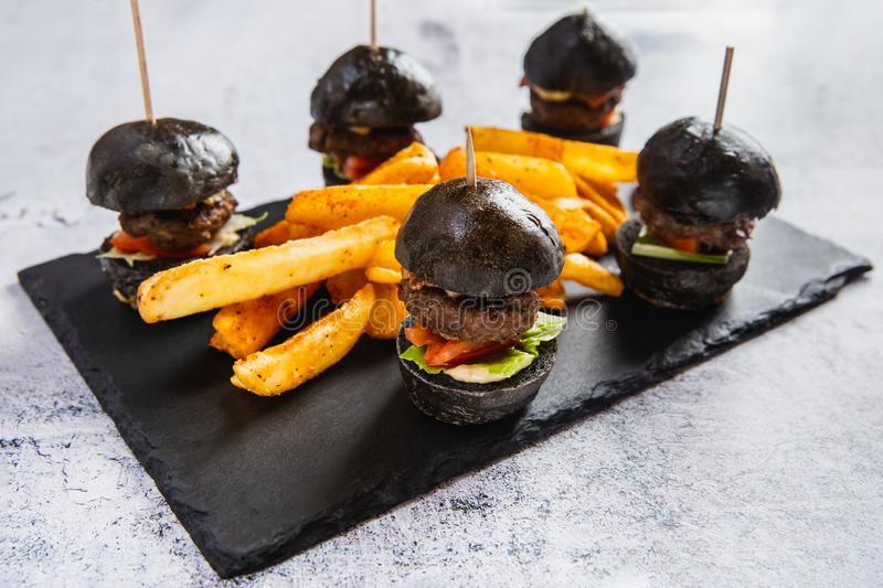Delicious mini black burgers with beef, tomato, cheese served with french fries on black table stock photo