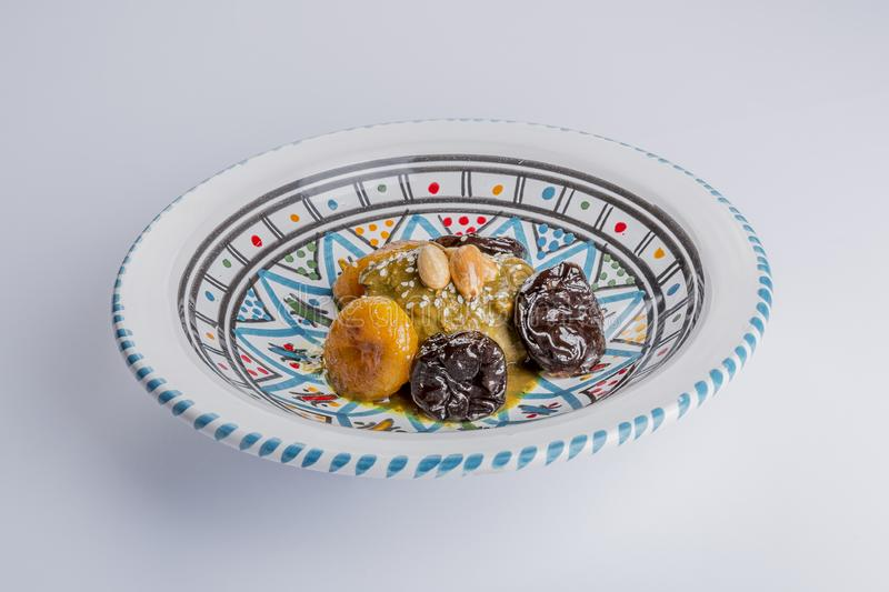 Delicious moroccan sweet dessert on a white ceramic plate decorated with blue, red, green and black colors. A delicious combination of color and texture stock images