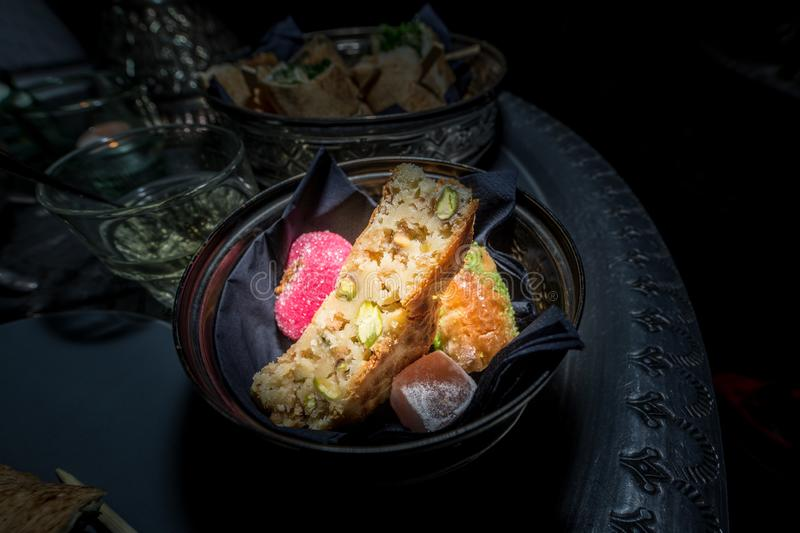 Delicious moroccan sweets in a ceramic plate on a metal tray with a black background. Traditional Moroccan treats at tea time stock image