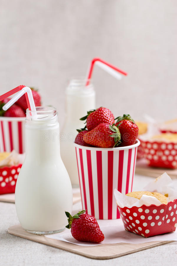 Delicious muffins, strawberries and milk in bottles. Selective focus stock photo