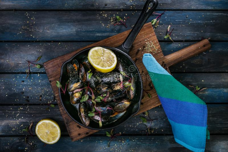 Delicious mussels. Serving on a hot frying pan with herbs spices and lemon on a colored wooden background. Top view.  royalty free stock image