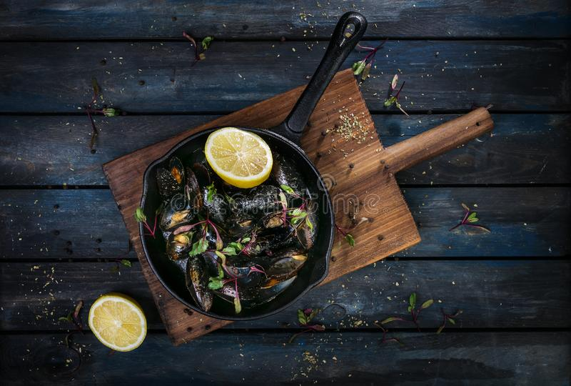 Delicious mussels. Serving on a hot frying pan with herbs spices and lemon on a colored wooden background. Top view.  stock photo