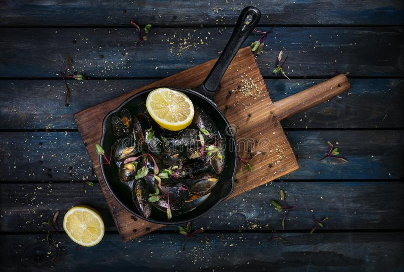 Delicious mussels. Serving on a hot frying pan with herbs spices and lemon on a colored wooden background. Top view.  royalty free stock photography