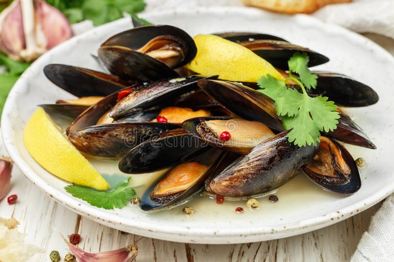 Delicious mussels in white wine with lemon, garlic, herbs and spices in a white plate. Baguette, Cilantro and pepper. Seafood. Clams in the shells. Snack for stock photography
