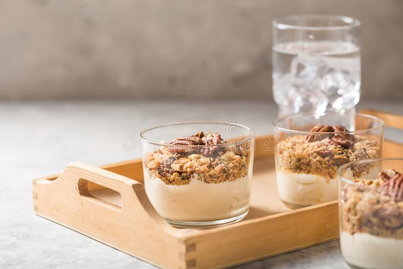 Delicious natural yogurt parfait with caramel, pecan nuts on conctere background stock photos