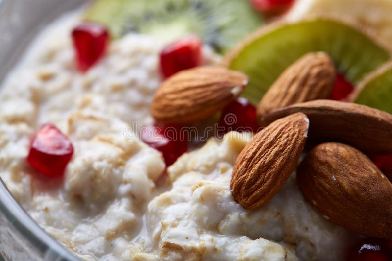 Delicious oatmeal porrige with fruits in glass bowl over rustic wooden background, shallow depth of field, close-up. royalty free stock images