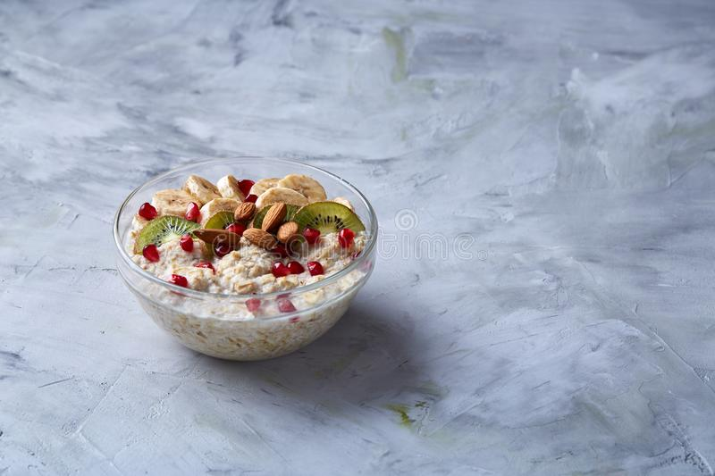 Delicious oatmeal porrige with fruits in glass bowl over white textured background, selective focus, flat lay, close-up. royalty free stock photography