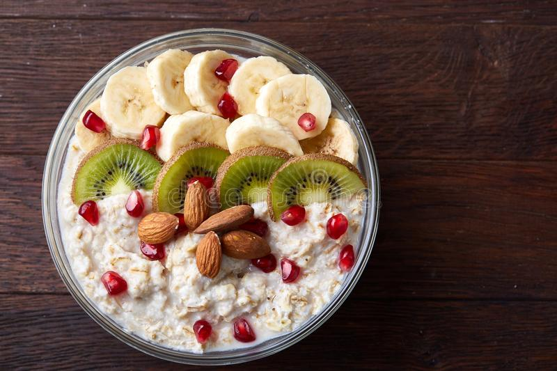 Delicious oatmeal porrige with fruits in glass bowl over rustic wooden background, selective focus, flat lay, close-up. stock photography