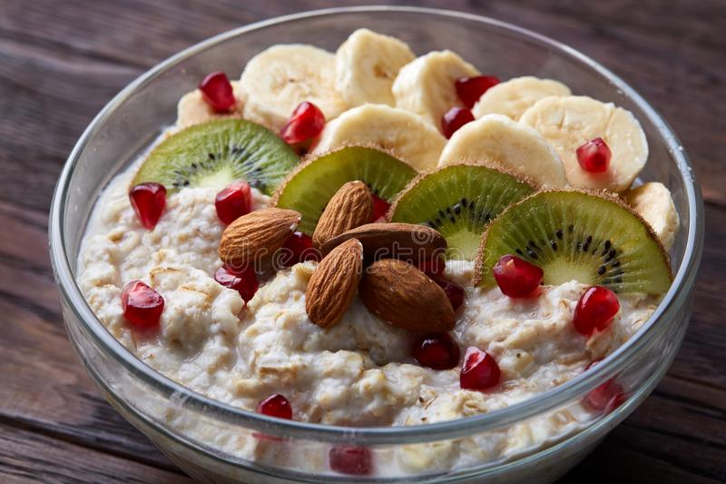 Delicious oatmeal porrige with fruits in glass bowl over rustic wooden background, shallow depth of field, close-up. royalty free stock photos