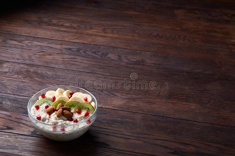 Delicious oatmeal porrige with fruits in glass bowl over rustic wooden background, shallow depth of field, close-up. stock photography