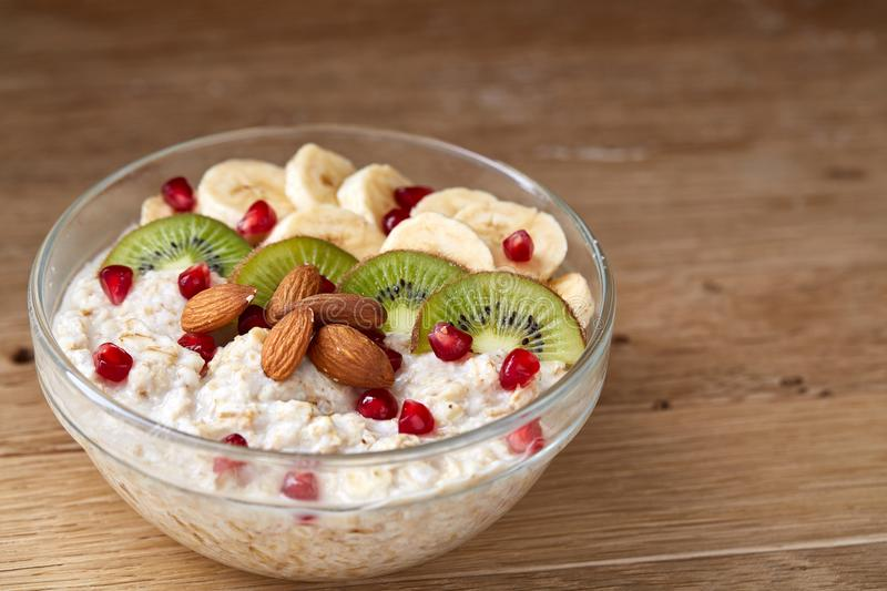 Delicious oatmeal porrige with fruits in glass bowl over rustic wooden background, shallow depth of field, close-up. royalty free stock photography