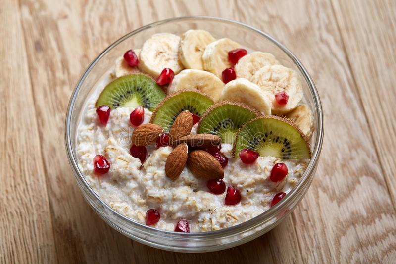 Delicious oatmeal porrige with fruits in glass bowl over rustic wooden background, shallow depth of field, close-up. stock image