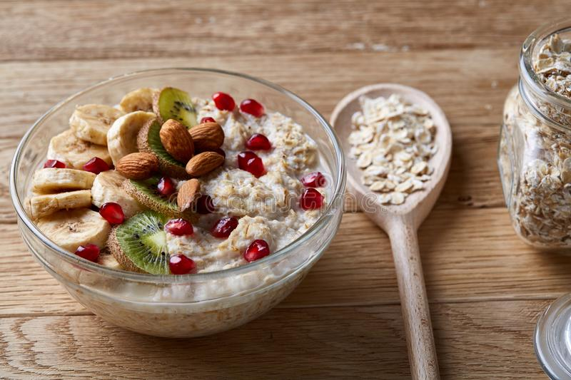 Delicious oatmeal porrige with fruits in glass bowl over rustic wooden background, shallow depth of field, close-up. stock images