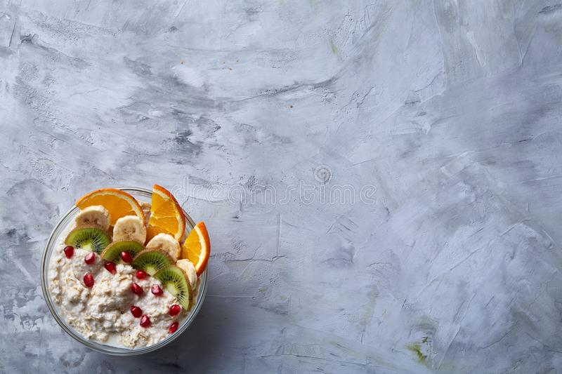 Delicious oatmeal with fruits in glass bowl isolated on white textured background, copy space, selective focus royalty free stock images