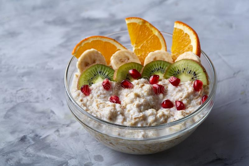 Delicious oatmeal with fruits in glass bowl isolated on white textured background, copy space, selective focus stock photo