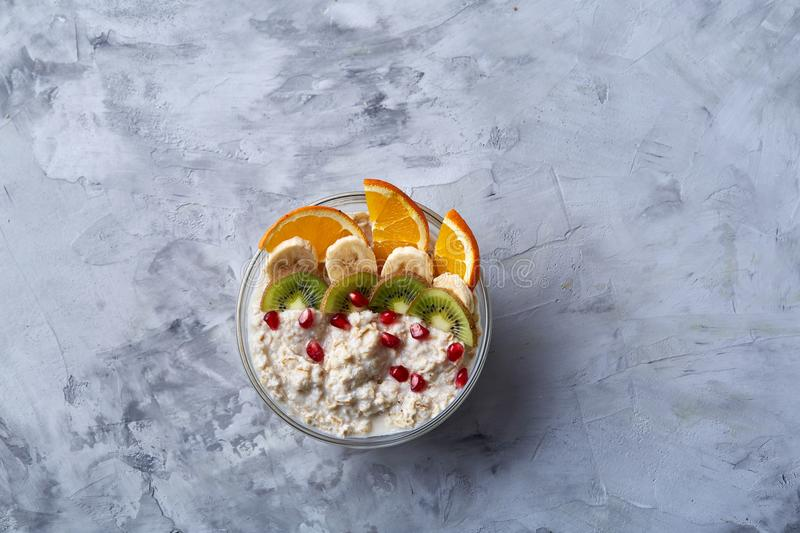 Delicious oatmeal with fruits in glass bowl on white textured background, copy space, selective focus stock images