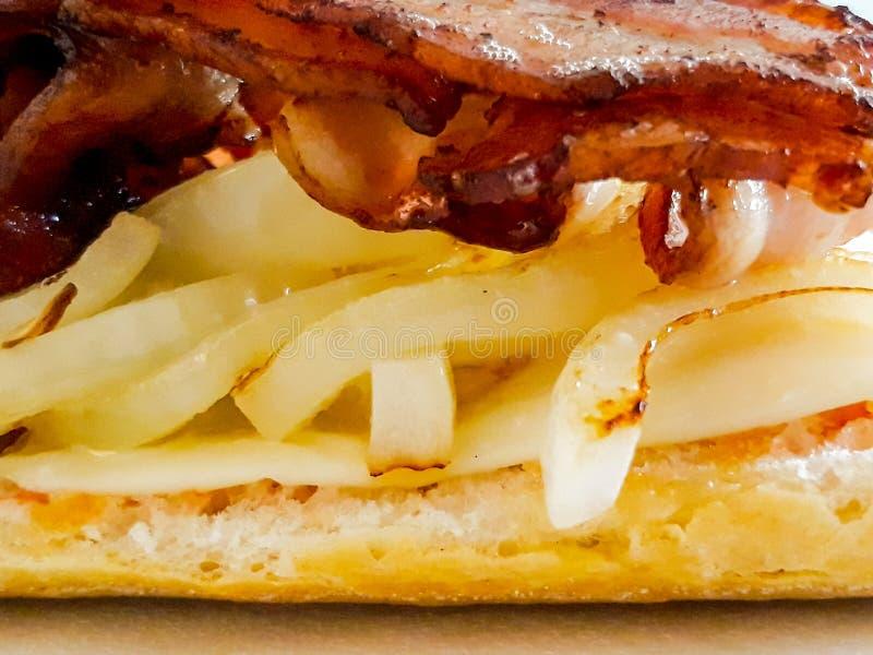 Bacon sandwich. Delicious open bacon sandwich with cheese and onion. Closeup. Horizontal image stock photos