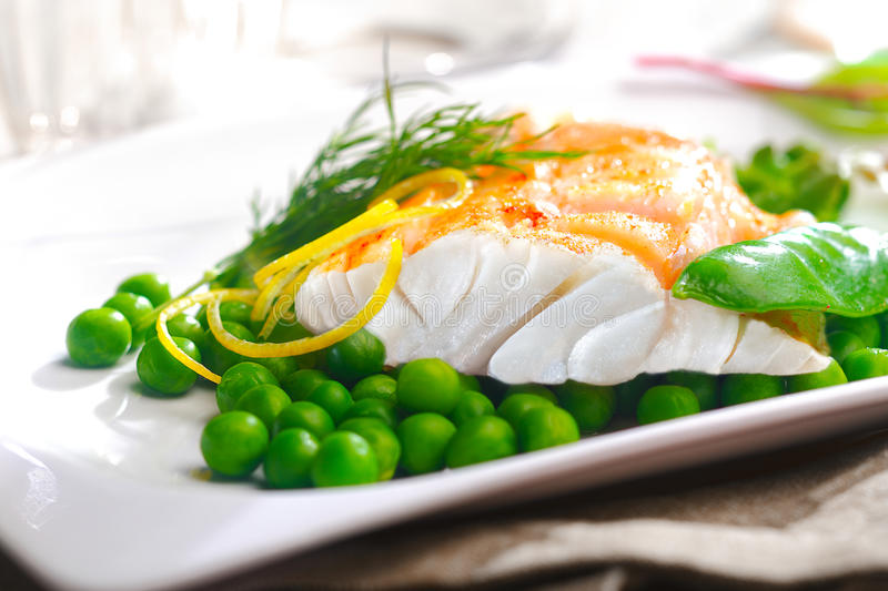 Delicious oven baked fish fillet with peas. Delicious oven baked fish or grilled fillet or steak with peas, a mangetout pod, lemon zest and fresh dill for a stock photo