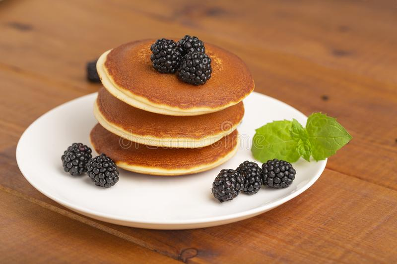 Delicious pancakes with BlackBerry and mint, on a white plate royalty free stock photos