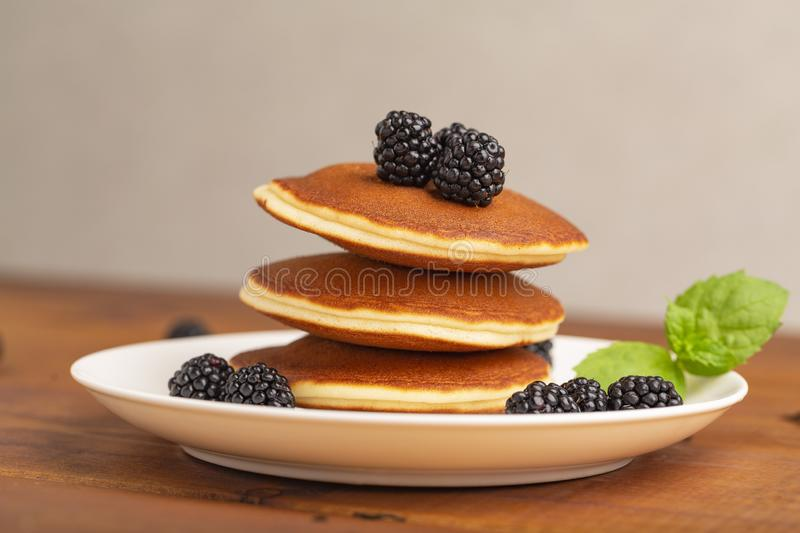 Delicious pancakes with BlackBerry and mint, on a white plate royalty free stock photography