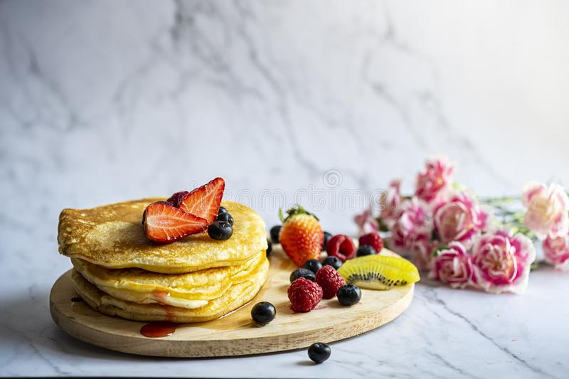 Delicious pancakes with fresh berries and honey on marble patterned floor with pink carnation and background royalty free stock photo