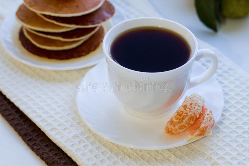 Delicious pancakes with honey and a cup of coffee on a white tab stock photo