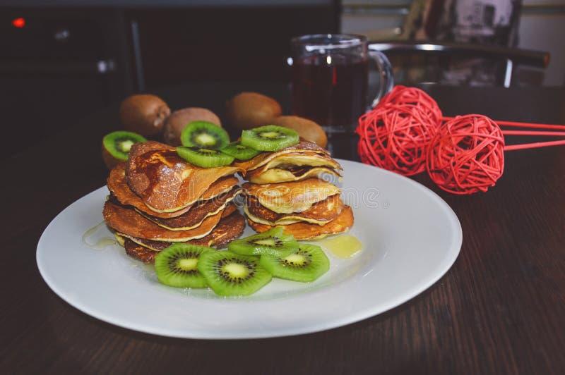 Delicious pancakes with kiwi. On wooden table royalty free stock photos