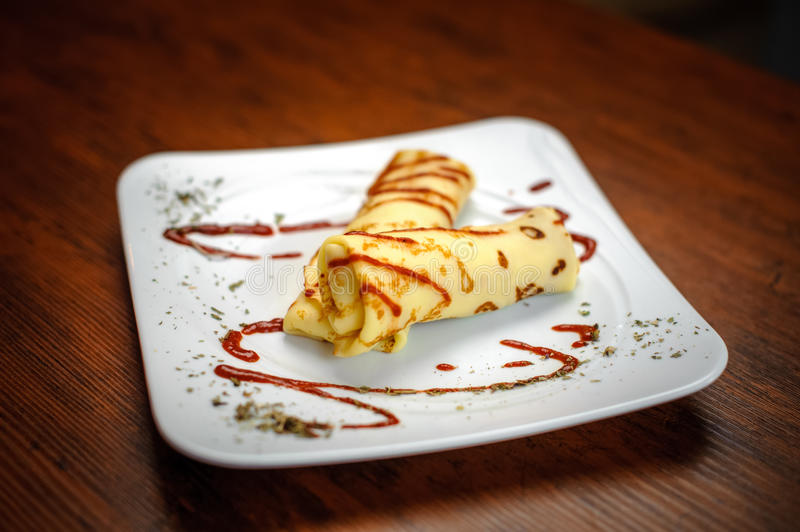 Delicious pancakes with meat, spices and sauce on a white plate royalty free stock image
