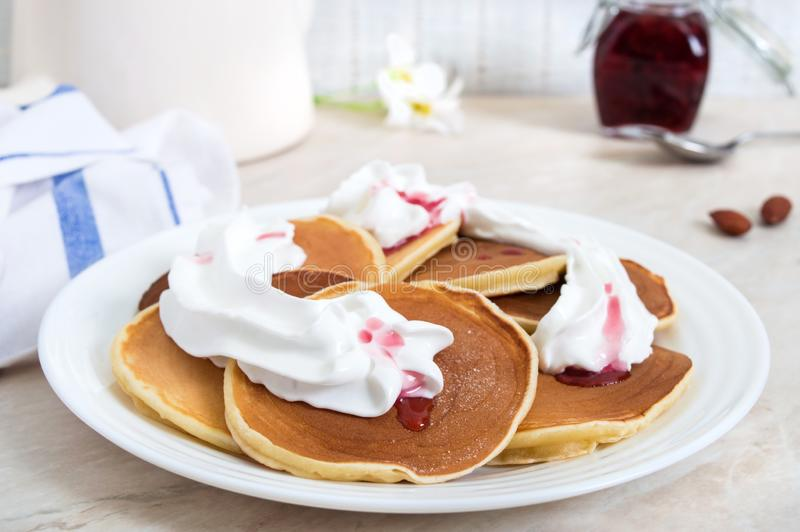 Delicious pancakes with raspberry jam and whipped cream on a white plate on the kitchen table. royalty free stock image