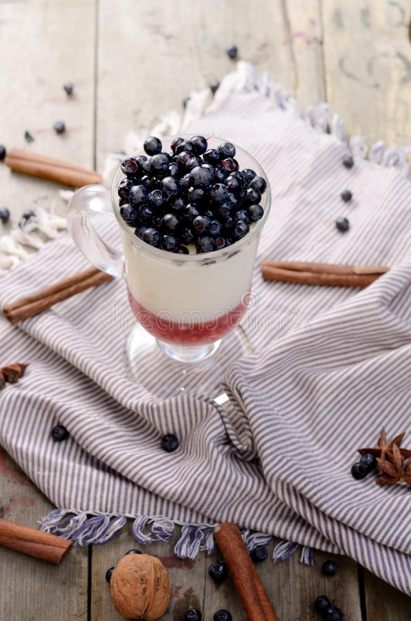 Delicious parfait dessert with bilberry, milk souffle and jello layers. Frozen treat in a glass on rustic wooden stock photo