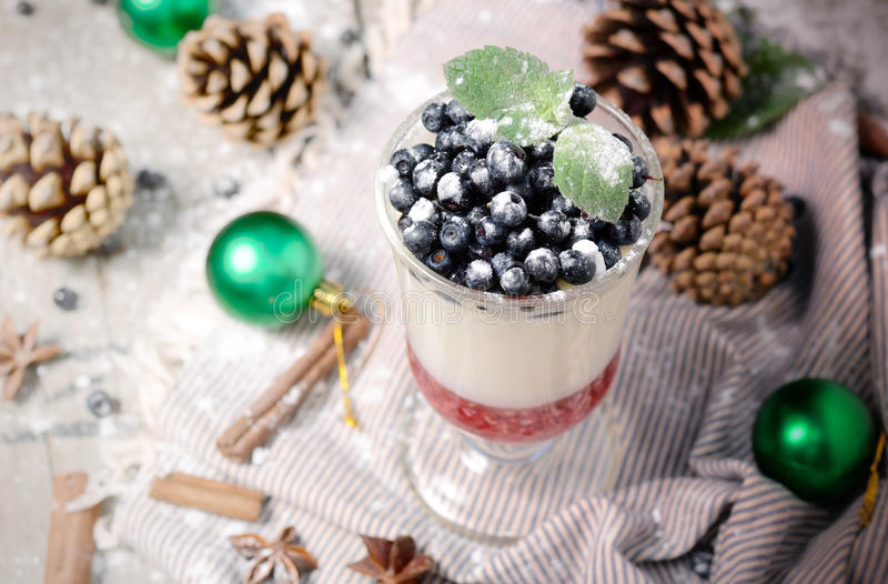 Delicious parfait dessert with bilberry, milk souffle and jello layers. Frozen treat in a glass on rustic wooden. Delicious parfait dessert with bilberry berries stock image