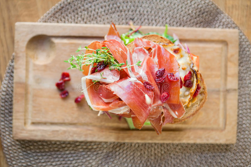 Delicious Parma Ham Sandwich On Wooden Plate. Closeup of delicious parma ham sandwich on wooden plate at cafe stock photo