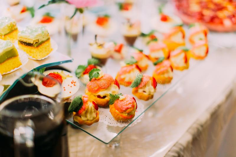 Delicious pastries with fruits are decorated with mint for wedding party. stock photo