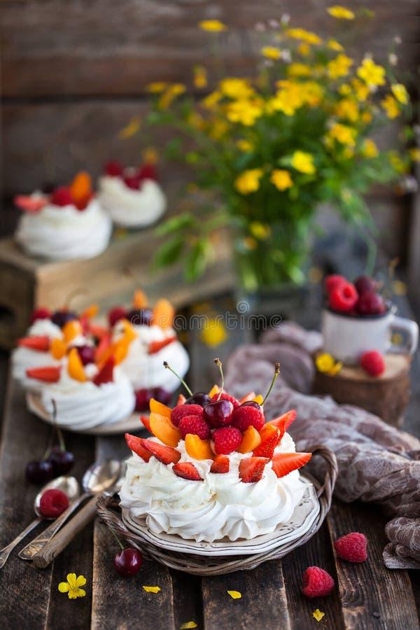Delicious Pavlova meringue cake decorated with fresh berries stock photos