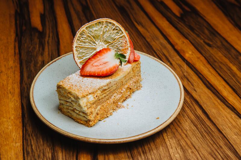 Delicious piece of honey cake. A delicious piece of honey cake is served with fresh strawberries on a plate that stands on a wooden background royalty free stock image