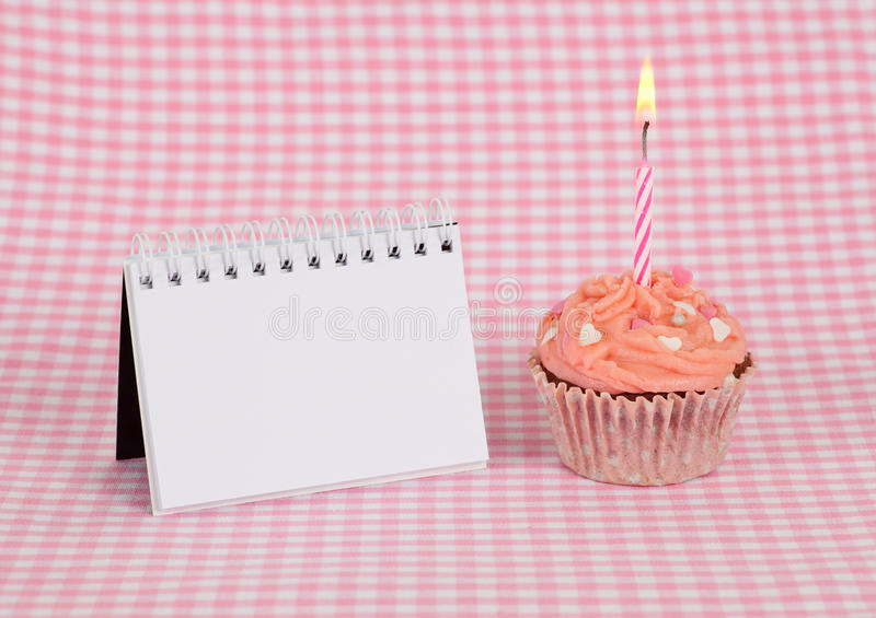 Delicious pink birthday cupcake with candle. And a blank note to leave a mesage. Insert your text here stock images