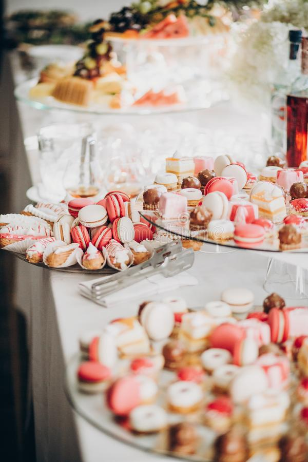 Delicious pink candy bar at wedding reception or christmas celebration. Pink and white macarons,cupcakes, desserts on stand, stock image