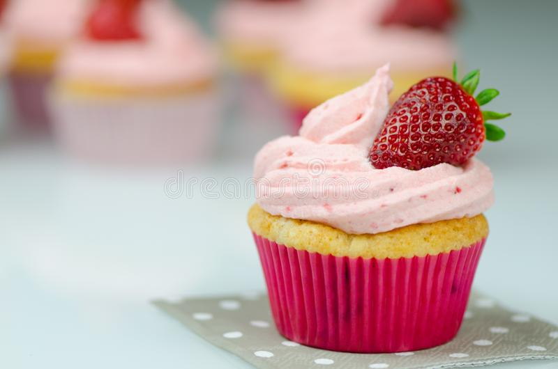 Delicious pink strawberry cupcake with a strawberry. Cupcakes and pink icing with a strawberries on top stock photography