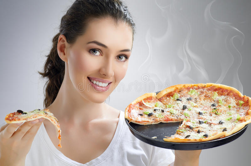 Delicious pizza. Girl eating a delicious pizza stock photography