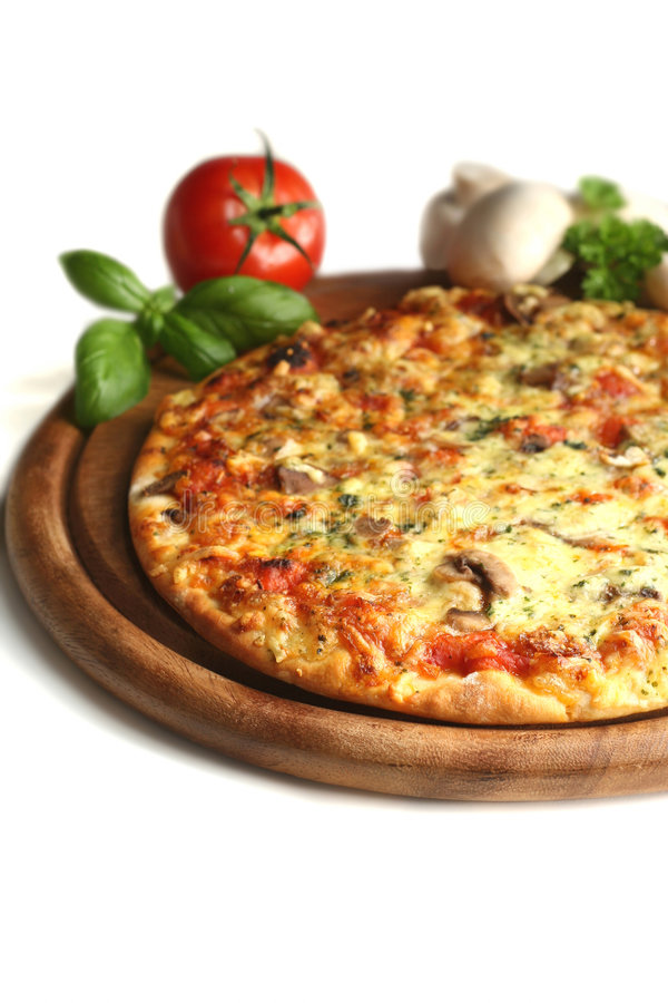 Delicious pizza. A delicious pizza served on a round wooden plate, white background stock photo