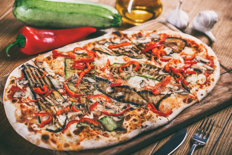 Delicious pizza with chicken, zucchini, eggplant, pepper, cheese and mushrooms on wooden rustic table. Top view. royalty free stock photos
