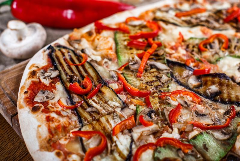 Delicious pizza with chicken, zucchini, eggplant, pepper, cheese and mushrooms on wooden rustic table. royalty free stock image