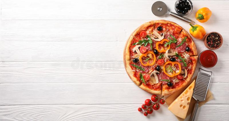 Delicious pizza and ingredients on white wooden background. Copy space stock photo