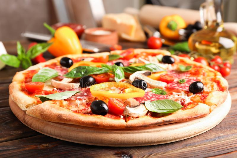 Delicious pizza and ingredients on wooden background. Close up stock photos