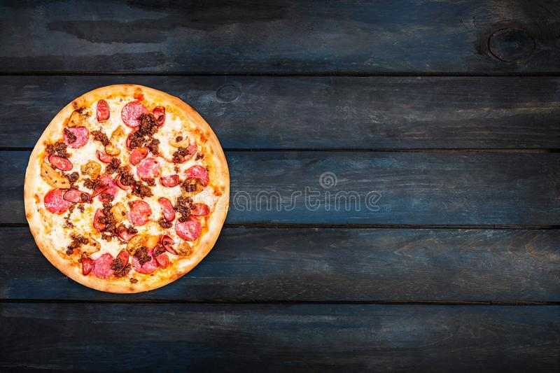 Delicious pizza meat mix with smoked sausage, chicken, minced meat, and pepperoni on a dark wooden background. Top view stock image