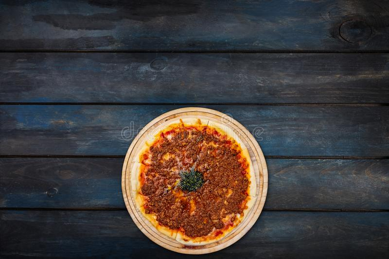 Delicious pizza with minced meat on a wooden stand on a dark wooden background. Top view bottom orientation royalty free stock images