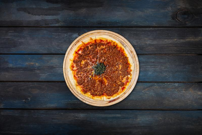 Delicious pizza with minced meat on a wooden stand on a dark wooden background. Top view center orientation stock image