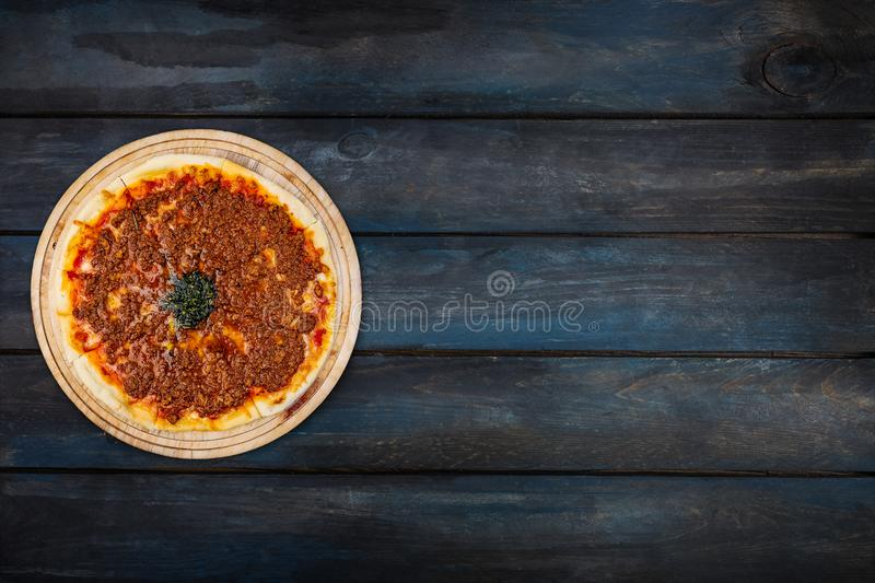 Delicious pizza with minced meat on a wooden stand on a dark wooden background. Top view orientation on the left side royalty free stock photography
